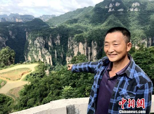"""彭齐云向记者介绍他的""""空中田园""""。 邓霞 摄"""