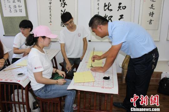 """""""孔子学堂""""的书法老师正在教学生们用毛笔写""""和""""字。 宋晓帆 摄"""