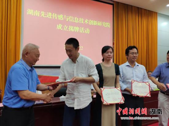 湘潭大学向北京大学教授团队颁发聘书。