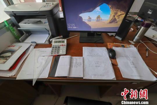8月7日,湖南龙山县茅坪乡国土所国土员彭鹏的办公桌子上摆放着没写完的笔记本。 张军 摄