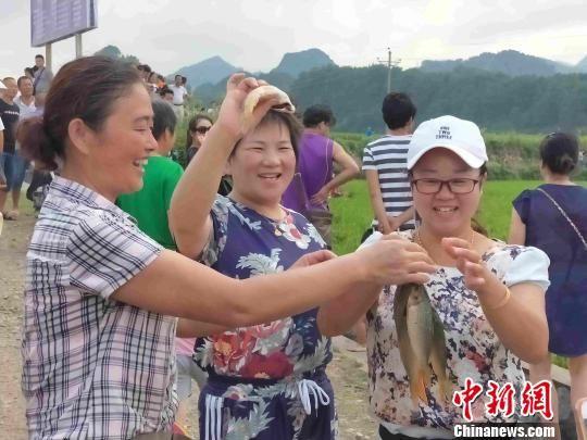 游客展示自己抓到的稻花鱼。 付敬懿 摄