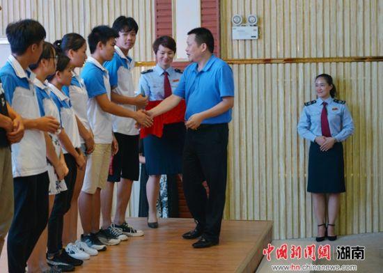 """连续两年参与""""与祖国共成长""""扶贫助学活动的湖南皇爷食品有限公司审计总监谢许伦向学生发放助学金。"""