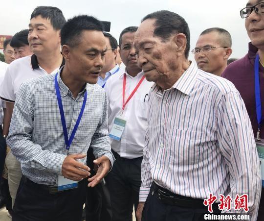 一位参加论坛的嘉宾正在与袁隆平交谈。 唐小晴 摄