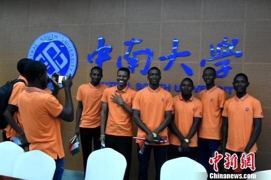 留学生们在中南大学校徽下自拍。 卢文伟 摄