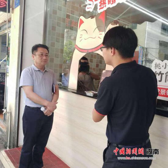 """詹志(右)向《半月谈》总编辑叶俊东介绍""""桃小江竹筒饭""""的经营情况。"""