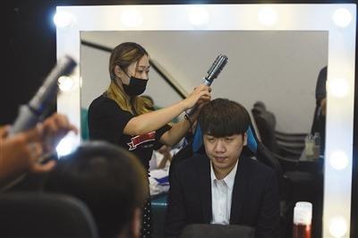 """化妆师给教练""""奶茶""""化妆。9月9日,电竞手们要出席一个与游戏迷的见面活动,商业化是目前电竞俱乐部一个重要的盈利方向。"""