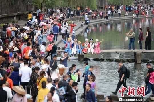游人身着少数民族服饰在人群中合影。 杨华峰 摄