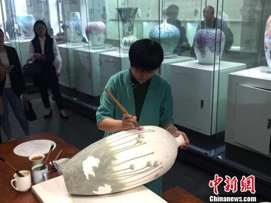 """中国陶瓷艺术大师黄小玲展示""""勾线分水""""技艺。 向一鹏 摄"""