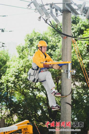 个人项目(绝缘操作杆作业法接引线):杆上作业人员正在安装绝缘挂架。