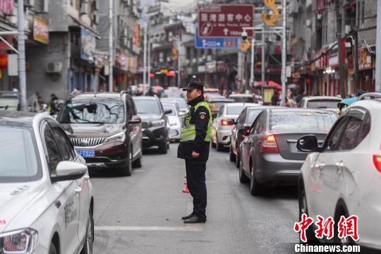 凤凰交警联合治安大队的工作人员正在道路中央指挥交通。 杨华峰 摄