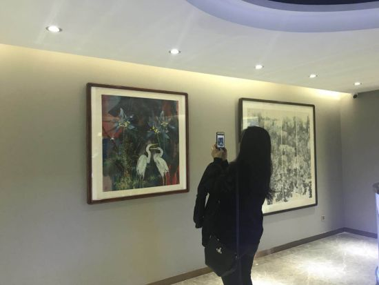 参观者对画作拍照。