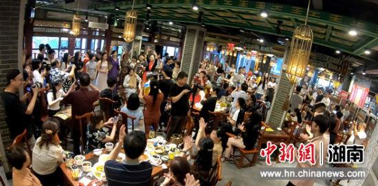 吟唱吸引了众多食客围观。