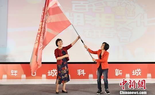 湖南省委常委、统战部部长黄兰香(左)向台湾主持人、研学营名誉团长黄智贤授营旗。 曹雄 摄