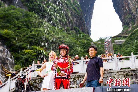 """耿杰(中)成功挑战攀爬999级石阶""""天梯""""。 吴光明 摄"""
