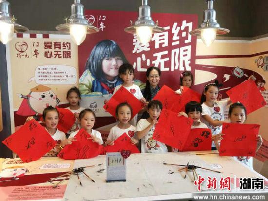 """江永女书国家级非遗传承人李爱莲与小朋友们为助力""""捐一元""""写下主题词。"""