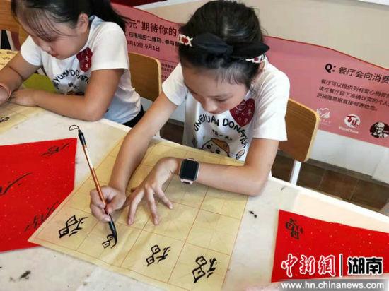 """小朋友在""""捐一元""""活动非遗体验区临摹学习江永女书。"""