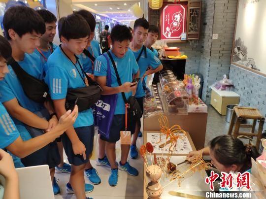 一个糖画制作小摊吸引数名日本青少年运动员围观。 王昊昊 摄
