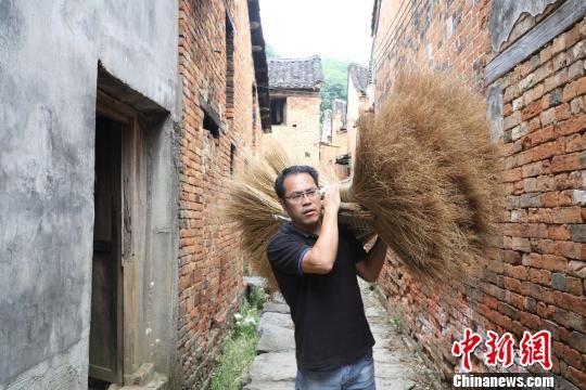 工作人员在村里收扫帚。 陈健林 摄