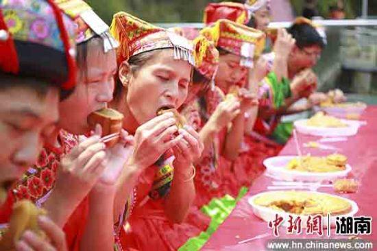 游客着瑶、畲服饰在玻璃栈道上吃月饼。