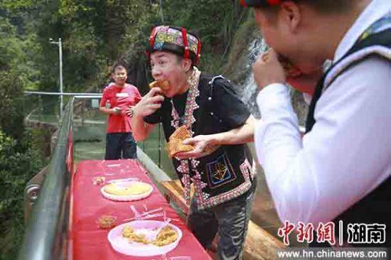 游客在玻璃栈道上大口吃月饼。