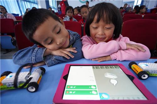 孩子们目不转睛地盯着平板编程页面,究竟它是如何操纵小小的机器人的呢?
