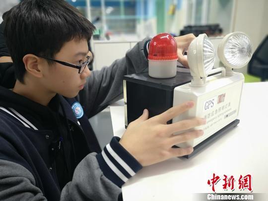 刘昕阳调试其创造作品可拆分式GPS消防应急灯。 刘曼 摄