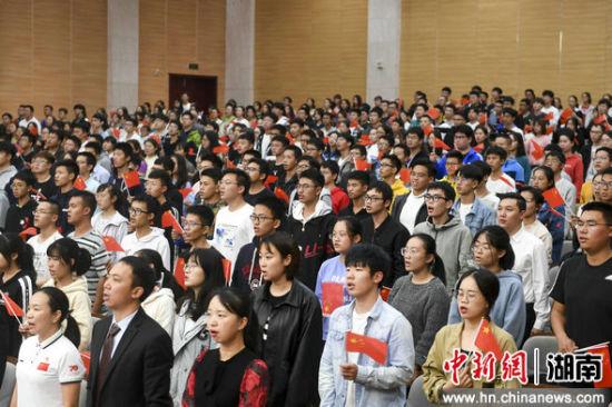 中南大学师生挥动国旗唱国歌。