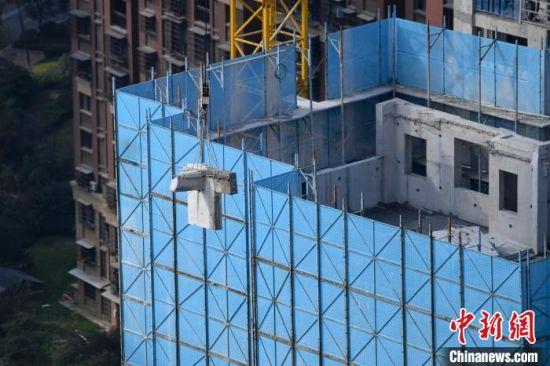 塔吊将切割后的水泥块吊运至地面。 杨华峰 摄