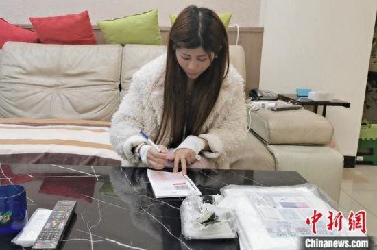 何爱英在台湾桃园填写快递单。江永县供图