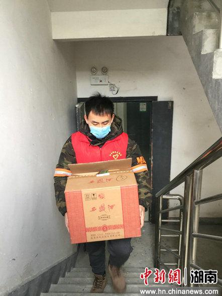 湘西土家族苗族自治州税务局的志愿者在挨户分送采购物资.