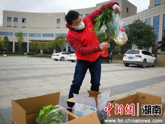 湘西土家族苗族自治州税务局的志愿者正对采购回来的物资进行消毒