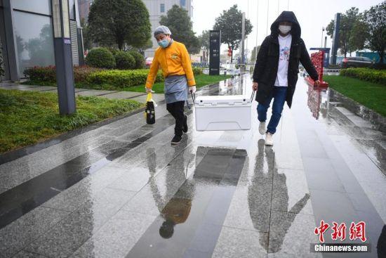 2月11日,两位店员将餐食放在保温箱为顾客送外卖。中新社记者 杨华峰 摄
