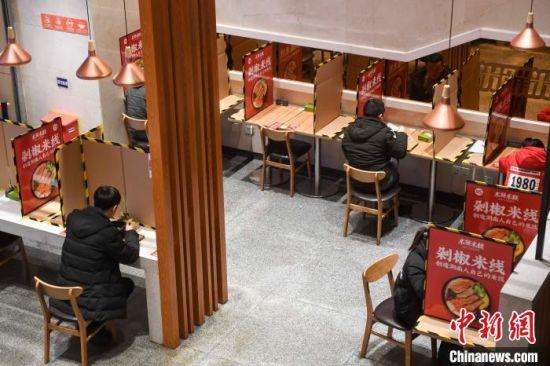 曾添华的一家店推出无接触、无交流就餐,餐桌之间设置隔离板防止交叉感染。 杨华峰 摄
