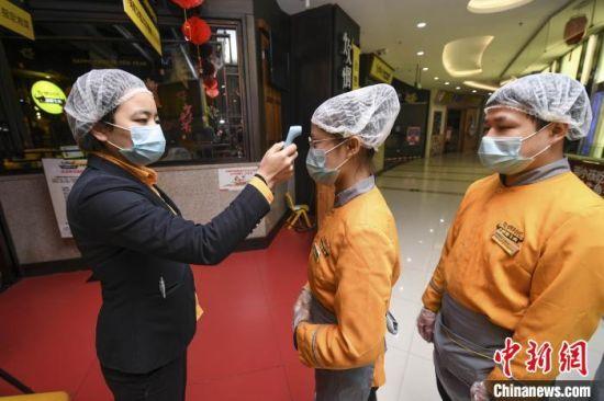 炊烟时代的一位餐厅店长为工作人员进行体温检测。 杨华峰 摄