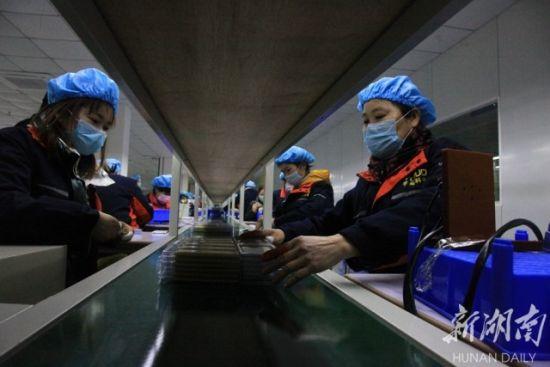 (2月20日,宁远县宇拓新能源科技有限公司,工人们戴着口罩、防护帽在锂电池生产线赶制订单。欧阳友忠 摄)