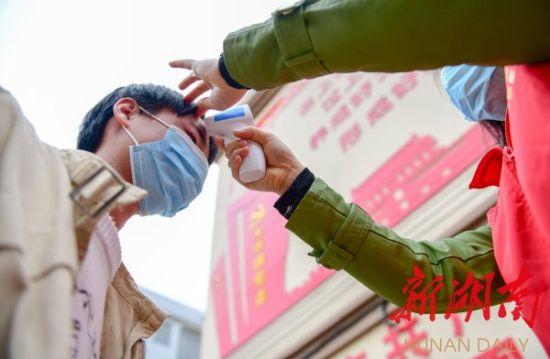 3月8日,道县东门街道冯家社区易地搬迁安置小区,妇联党员干部在给贫困户测体温。蒋克青 朱号荣 摄影报道