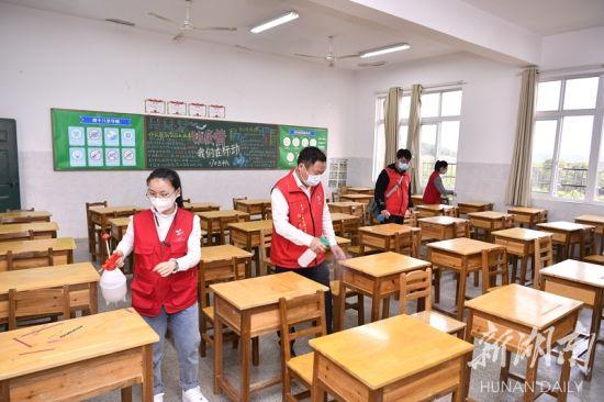 杨士泉(左二)和志愿者们在为已复学的教室做消杀。 湖南日报·新湖南客户端记者 童迪 摄