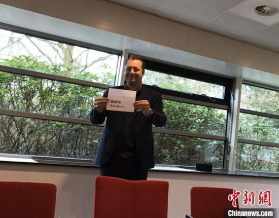 """荷兰卫生部疾病防控中心主任斯文・德・兰根手持""""谢谢你""""中文字样。湖南省委统战部供图"""