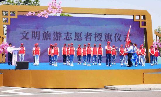 活动现场为文明旅游志愿者服务队代表授旗。
