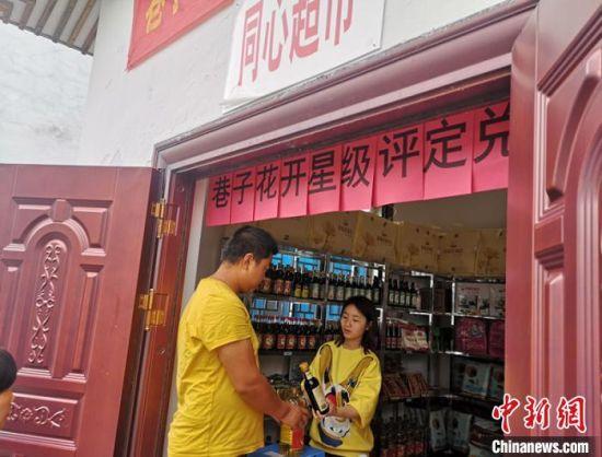 """村民在""""同心超市""""兑换生活物资。 刘曼 摄"""