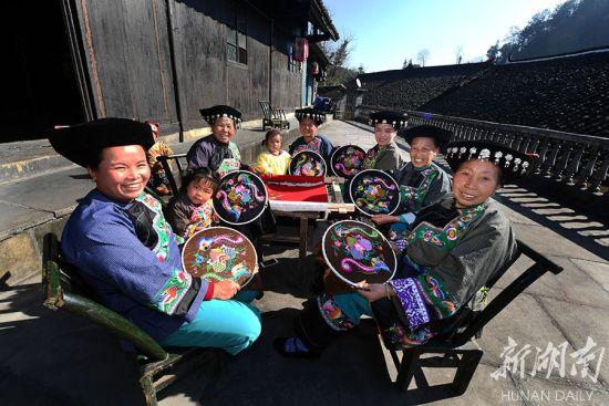 (十八洞村老支书石顺莲家院子里,几名苗家妇女在绣制苗绣,每人每月平均能领到工资1500多元。郭立亮摄)