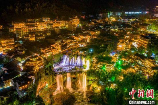 夜空中的古镇与瀑布。 杨华峰 摄