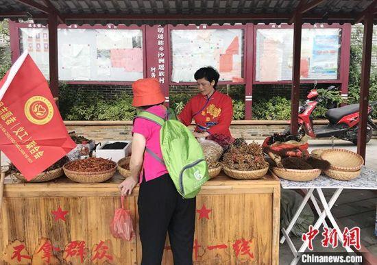 """图为6月15日,""""半条被子""""纪念广场边的小摊上,村民招呼着游客尝鲜、购买土货。 中新社记者 邓霞 摄"""