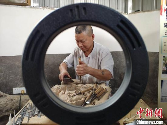 在朱有志的鼓励下,开慧村人陈拥军建起了自己的木雕工作室。 王昊昊 摄