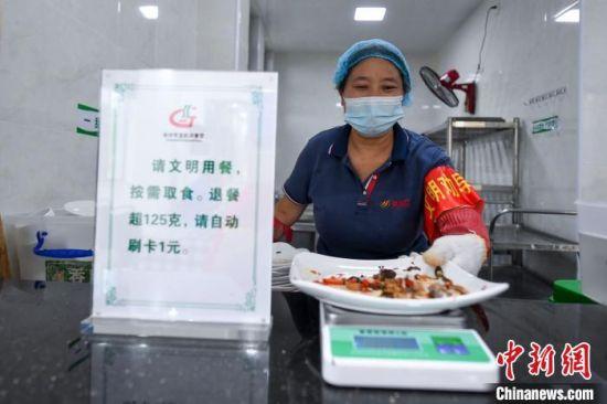 工作人员将餐盘放入回收处的克秤称重。 杨华峰 摄