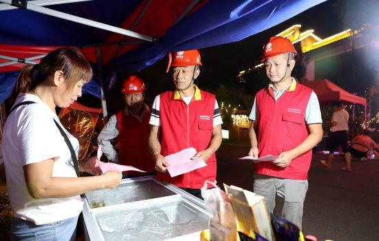 工作人员向夜市摊主宣传安全用电知识。