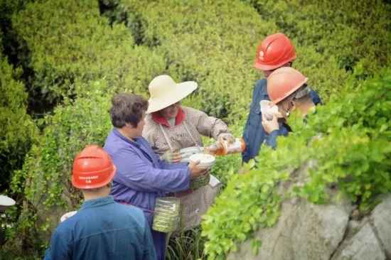茶农热情地给巡线的供电公司员工倒茶。盛睿 摄