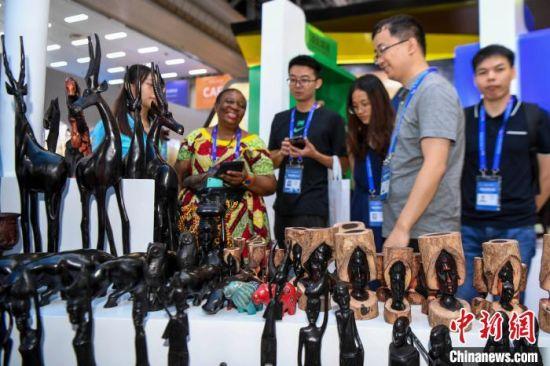 2019年6月,在湖南长沙举行的首届中国-非洲经贸博览会上,来自非洲的手工艺品吸引参观者驻足咨询。  杨华峰 摄