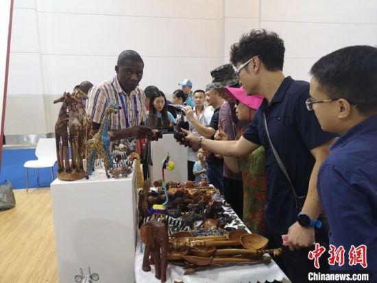 首届中国-非洲经贸博览会期间,非洲参展商向观众介绍商品。 杨华峰 摄