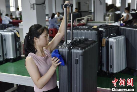蓝山县皮具箱包科技产业园,员工正在擦拭箱子。 杨雄春 摄